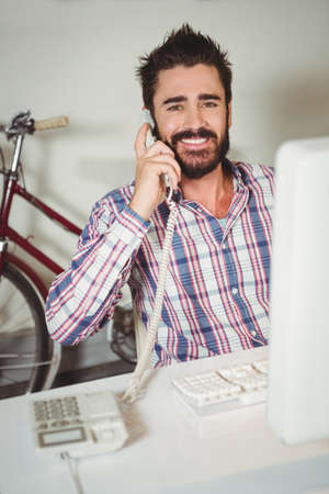 landline phone: Portrait of happy man talking on landline phone by computer at creative office