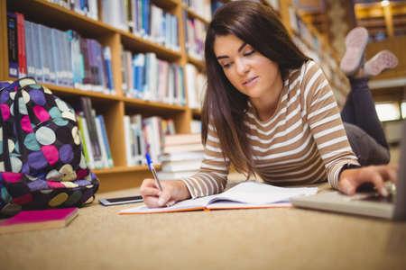 tasking: Portrait of female student multi tasking while lying on floor in library LANG_EVOIMAGES