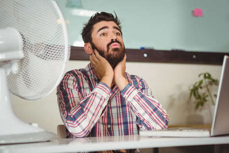 electric fan: Businessman suffering from neck pain by electric fan at creative office