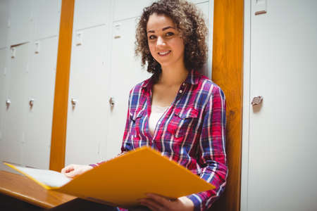 locker room: Pretty student reading in the locker room at the college