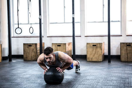 man working out: Fit man working out with ball at crossfit gym
