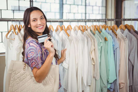 clothes rack: Woman holding credit card while standing against clothes rack in shop