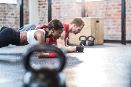planking: Muscular couple doing planking exercises in crossfit