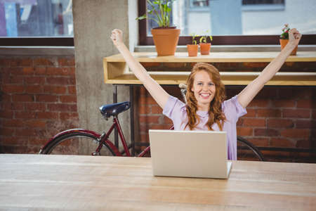 hands raised: Happy woman with hands raised at office