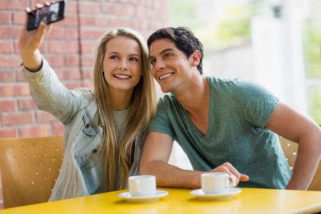tomando refresco: Los estudiantes que toman autofoto en el caf� en la universidad LANG_EVOIMAGES