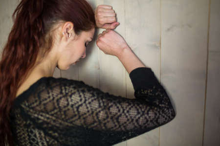 tensed: Tensed woman with eyes closed while leaning against wall LANG_EVOIMAGES