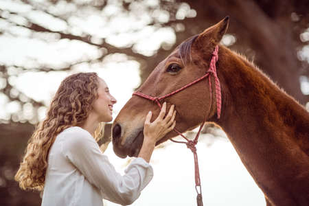 Young woman with her horse in the countryside LANG_EVOIMAGES