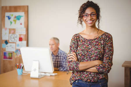 computer tech: Portrait of businesswoman smiling with arms crossed while colleague working in background