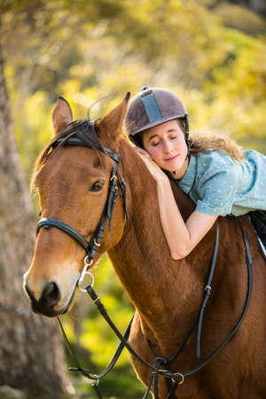 reigns: Happy woman hugging her horse in the countryside