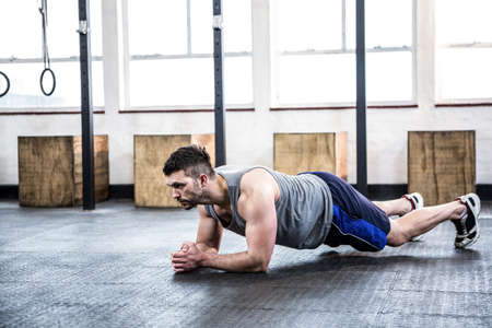 working out: Fit man working out in plank at crossfit gym LANG_EVOIMAGES