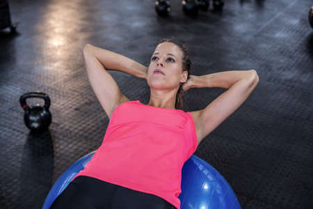 crunches: Woman doing abdominal crunches on fitness ball in crossfit gym LANG_EVOIMAGES