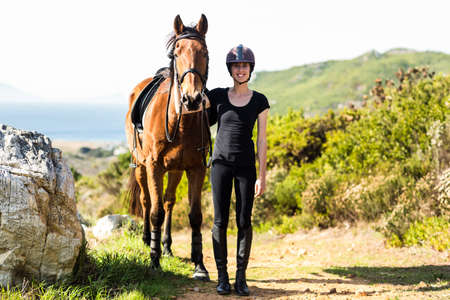 reigns: Happy woman walking with her horse in the countryside
