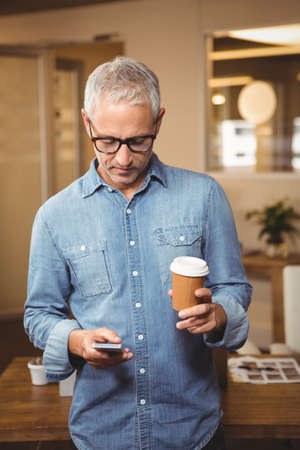disposable cup: Creative businessman holding disposable cup while using smartphone in office