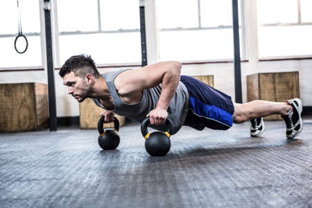 man working out: Fit man working out with kettlebells at crossfit gym