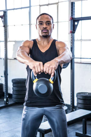 working out: Fit man working out with kettlebell at crossfit gym