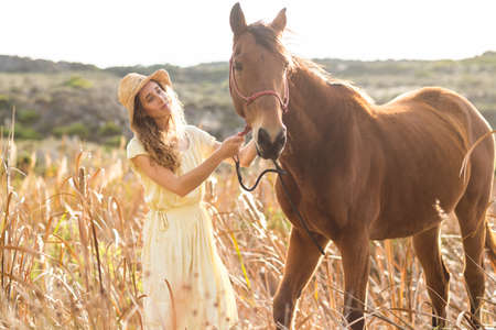 reigns: Young happy woman walking with her horse in the countryside LANG_EVOIMAGES