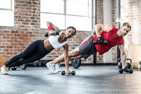 raises: Fit couple doing dumbbell rows in crossfit LANG_EVOIMAGES