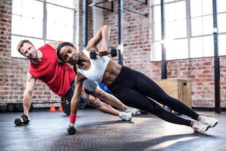 adult hand: Fit couple doing dumbbell rows in crossfit LANG_EVOIMAGES