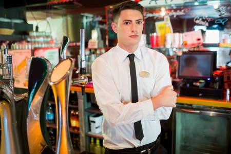 well dressed: Well dressed barkeeper with crossed arms in pub
