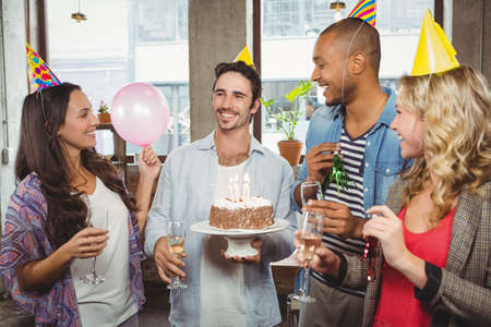 celebratory event: Man holding birthday cake while colleagues wearing caps and drinking champagne at event
