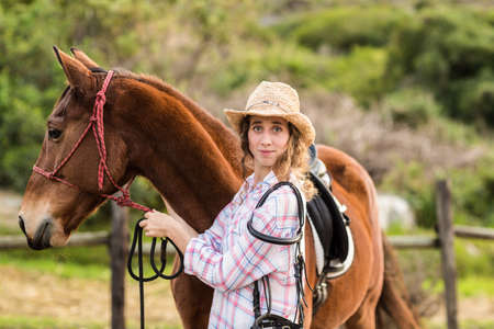 reigns: Young woman with her horse in the countryside LANG_EVOIMAGES