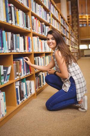 mujer arrodillada: Retrato de mujer joven de rodillas mientras toma el libro del estante de biblioteca LANG_EVOIMAGES