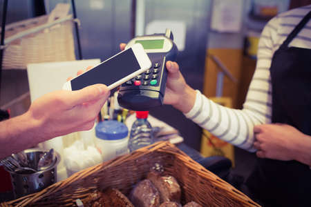 pin entry: Customer paying with mobile phone at the cafe