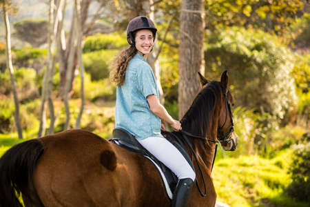 reigns: Young woman riding her horse  in the countryside