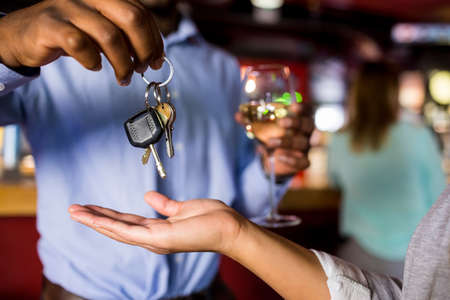 designated: Man drinking wine giving car key to woman at the bar