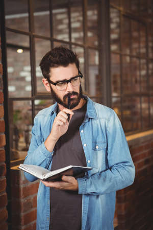 man holding book: Thoughtful man holding book while looking away LANG_EVOIMAGES