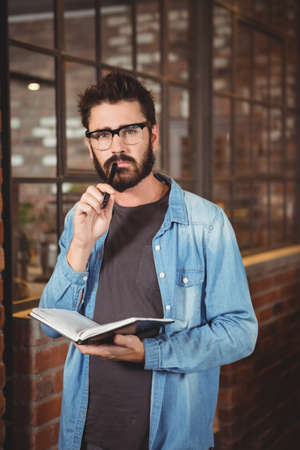 man holding book: Portrait of thoughtful man holding book while looking away