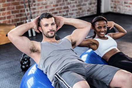 sit up: Fit man and woman doing sit ups on exercise ball in crossfit