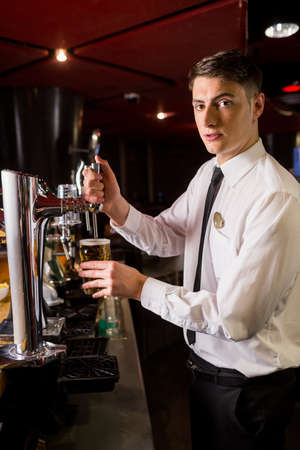 well dressed: Well dressed bartender serving beer in a bar