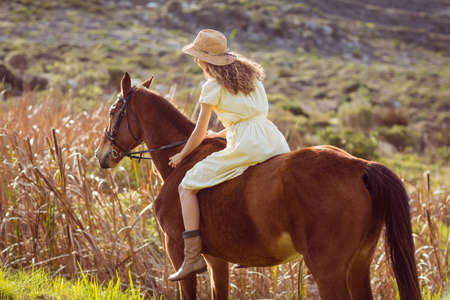 Young woman riding her horse in the countryside LANG_EVOIMAGES