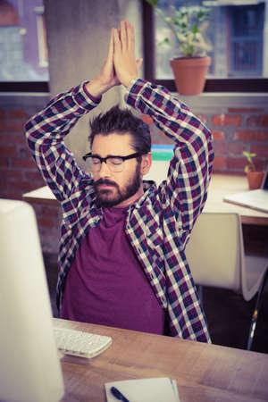 manos levantadas: Empresario meditando con las manos levantadas en la oficina creativa LANG_EVOIMAGES