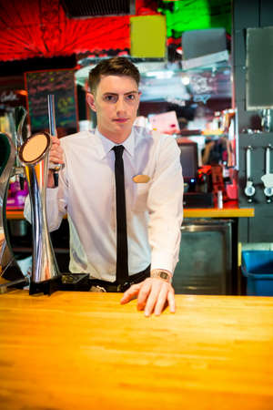 well dressed: Well dressed barkeeper looking at the camera behind counter LANG_EVOIMAGES