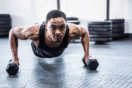 working out: Fit man working out with dumbbells at crossfit gym