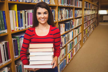 carrying heavy: Portrait of female student carrying heavy books while standing in library LANG_EVOIMAGES