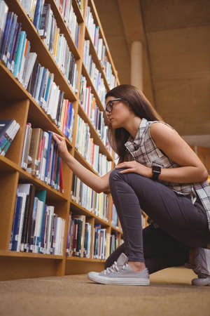 selecting: Low angle view of young student selecting book from shelf LANG_EVOIMAGES