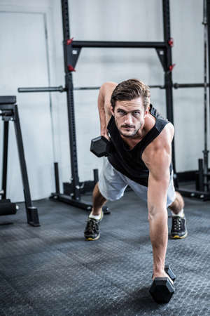man working out: Fit man working out with dumbbells at crossfit gym
