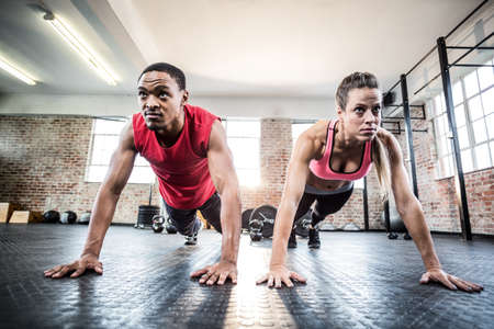 push ups: Fit couple doing push ups in crossfit gym LANG_EVOIMAGES