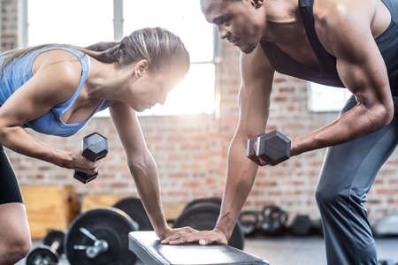 lean out: Fit couple doing dumbbell exercises in crossfit gym