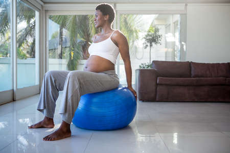 prenatal care: Pregnant woman sitting on exercise ball and looking away at home
