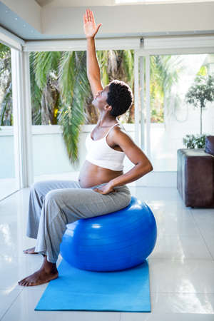 ball stretching: Pregnant woman stretching while sitting on exercise ball at home LANG_EVOIMAGES