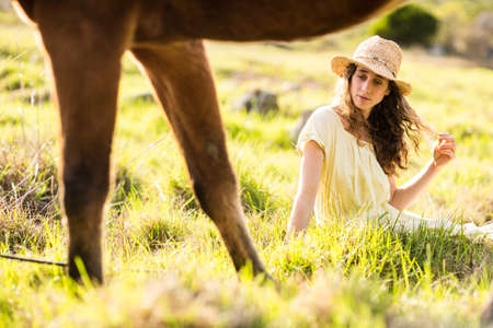 reigns: Young calm woman with her horse in the countryside