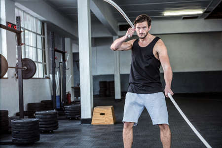 man working out: Fit man working out with battle ropes at crossfit gym