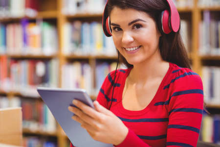 bookshelf digital: Cheerful student holding tablet and wearing headphones against bookcase