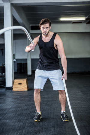 working out: Fit man working out with battle ropes at crossfit gym