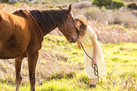horse love horse kiss animal love: Young smiling woman with her horse in the countryside LANG_EVOIMAGES