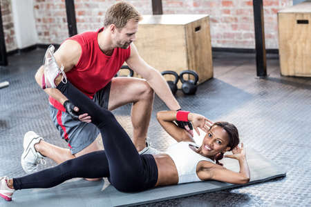 sit up: Muscular couple doing abdominal exercises in crossfit